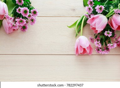Pink tulips and chrysanthemum flowers on wooden background, copy space.