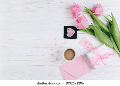Pink tulips, envelope, gift, cup of coffee and paper hearts on white wooden background, copy space and flat lay. Mother's Day concept.
