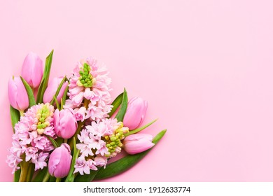 Pink tulips and pink hyacinths flowers bouquet on a pink background. Top view, copy space for text