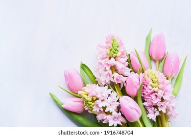 Pink tulips and pink hyacinths flowers bouquet on a light background. Top view, copy space for text