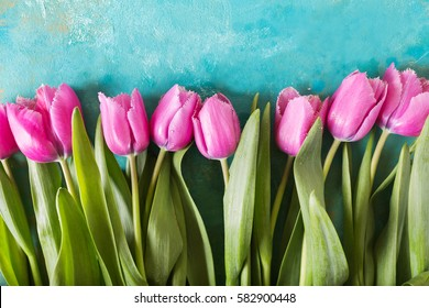 Pink tulips on turquoise abstract background.