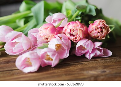 Pink tulips on the wooden background.