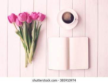 Pink tulips over white wood table