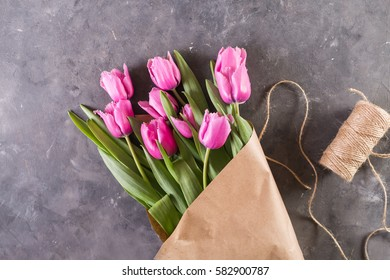 Pink tulips in a package of crafton gray abstract background.
