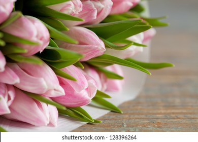 Pink tulips in paper pack on wooden background