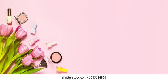 Pink tulips and some cosmetic on pink spring background, top view, flat lay. Copy space for text