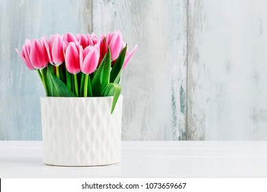 Pink tulips in white ceramic vase, blue wooden background.