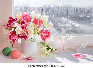 Pink tulips and white freesia flowers with Easter decorations on the window board, sunshine after rain