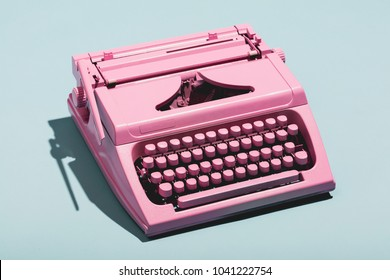Pink typewriter on a blue pastel background. Vintage machine. Journalism.