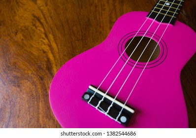 Pink ukulele on brown wooden background.Some countries call it ukelele.Is a kind of instrument Looks like a guitar with 4 strings.shape same the guitar.