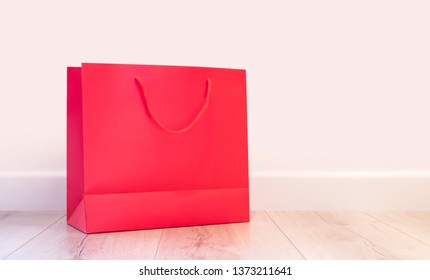 Pink unbranded shopping bag on the floor