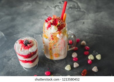 Pink unicorn milkshake with whipped cream and dessert, dripping sauce and candy