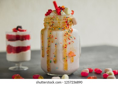 Pink unicorn milkshake with whipped cream and sweet dessert, dripping sauce and candy