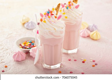 Pink unicorn milkshakes with whipped cream, sugar and sprinkles