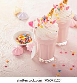Pink unicorn milkshakes with whipped cream, sugar and sprinkles
