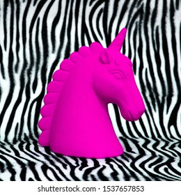 Pink unicorn souvenir on zebra print background Minimal art
