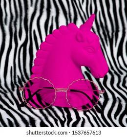 Pink unicorn souvenir and stylish sunglasses on zebra print background. Minimal fashion art
