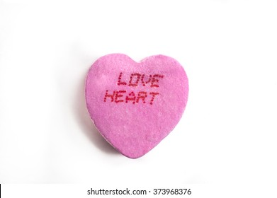 Pink Valentine's Day candy heart with Love Heart text word on white background