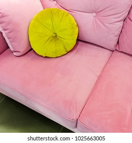 Pink velvet sofa with fancy lime green cushion. Luxurious furniture.