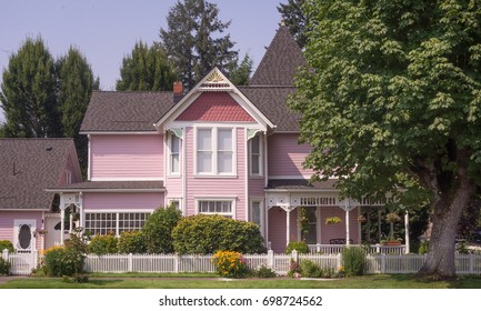 Pink Victorian home beside a stately maple tree.