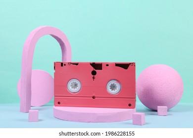 Pink video cassette on the podium with geometric shapas. Concept art. Fashion Minimalism