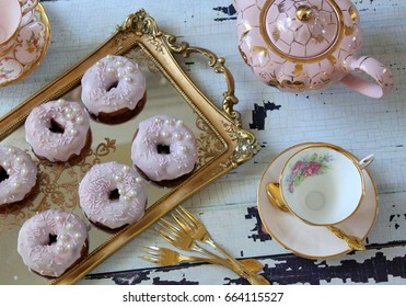 Pink vintage tea cup and saucer on a distressed wood table with pink iced donuts on a gold tray and teapot - afternoon tea party