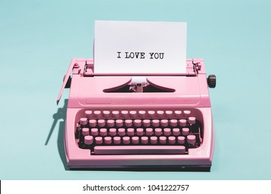 "Pink vintage typewriter with a white sheet of paper and ""I love you"" written on it. Love concept."