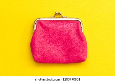 Pink wallet on yellow background . Close up. Top view.