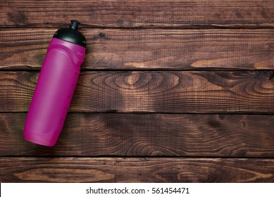 Pink water bottle on brown wood plank background. Top view