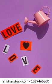 Pink watering can Love sign on pastel purple background flat lay with shadow Creative minimalism pop art composition. Valentines day banner minimal style. Romantic love backdrop greeting card design.