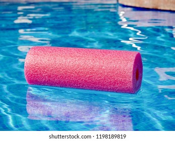 pink water-swirl (dumbbell) on sun-flooded blue mosaic covered water of a pool in closeup. The water is slightly moved and it shows a reflection.