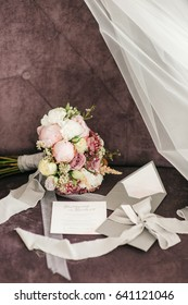 Pink wedding bouquet and grey envelopes lie on the violet chair