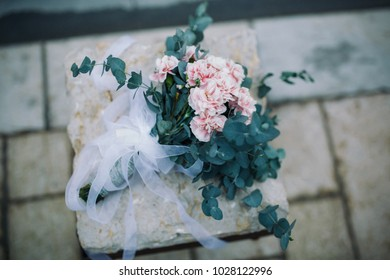 pink wedding bouquet lies on a stone outdoors against a gray wall background top view