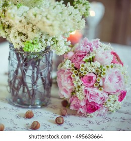 Pink wedding bouquet lies on the table surrounded with nuts