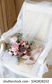 Pink wedding bouquet of peonies and shoes lying on the chair