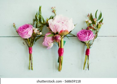 pink wedding boutonnieres with roses and peonies