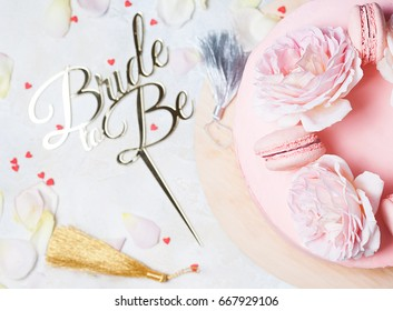 Pink Wedding cake with roses and macaroons with topper Bride to be. Top view, flat lay.