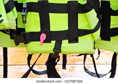 Pink whistle on green yellow life jacket hanging on the boat for safely of passengers