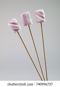 Pink and white bicolor marshmallows on wooden skewer sticks, isolated on light gray background