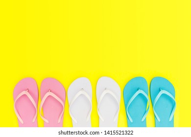 Pink, white, blue flip flops shoes on yellow background, top view, copy space. Toe sandals, flat lay, text place. Summer background with flipflop shoes.
