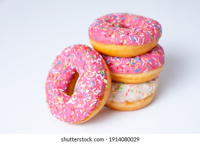 Pink and white doughnuts close up on a white background. High quality photo
