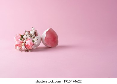 Pink and white flowers fallng out of eggshell on a pink background, close up. Easter background.