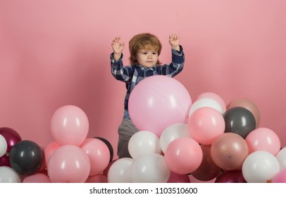 Pink, white and gray balloons for celebration. Funny kid play on his own on pink background. Cute boy wearing blue shirt. Clothes for children