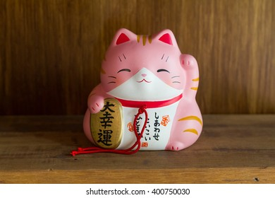 pink and white maneki-neko cats cute lucky mascot of Japanese, with Chinese and Japanese text on wooden shelves.