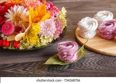 pink and white marshmallows (zephyr) on a round wooden board with floral composition on a gray wooden background.