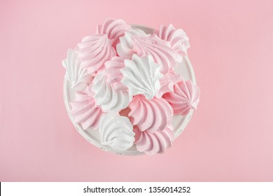 Pink and white meringue on white stand. Pink background.