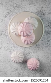Pink and white meringues on white plate. Flat lay on concrete background.
