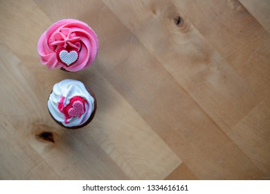 pink and white muffins on wooden ground whipping cream and heart in top view
