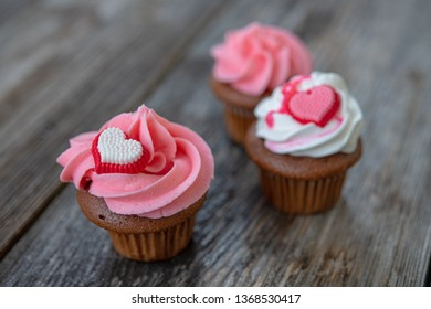 pink and white muffins on wooden ground with heart whipping cream