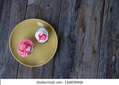 pink and white muffins on wooden ground whipping cream and heart